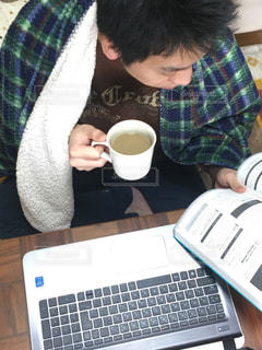 ノートパソコンと参考書を使って勉強してる人の写真・画像素材[2917290]