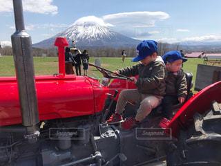 羊蹄山をバックにトラクターに乗る兄弟の写真・画像素材[2685262]