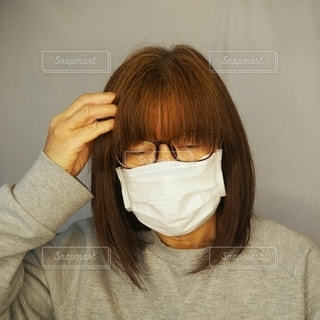 頭痛がして苦しい表情の50代の女性。の写真・画像素材[2940119]