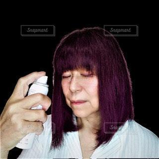 目をつぶって美容スプレーを顔にかける60歳の日本人女性の写真・画像素材[3699134]