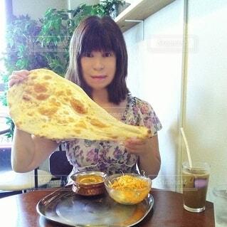60歳の女性が持つ、顔より大きなナンの写真・画像素材[3700436]