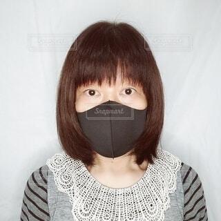 黒いマスクをして正面を向いている60歳の女性の顔の写真・画像素材[3731381]