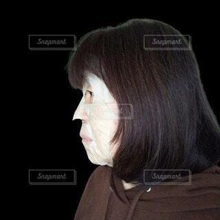 紙パックをしている横向きの六十歳の女性の写真・画像素材[3759952]
