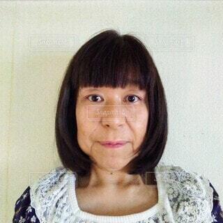 正面を向いて微笑む60歳の女性のポートレートの写真・画像素材[3782820]