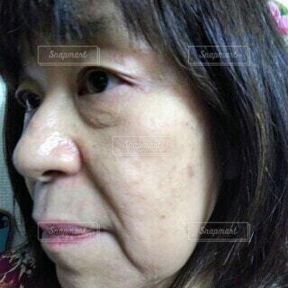 六十歳の女性の頬のたるみやほうれい線のクローズアップの写真・画像素材[3826207]