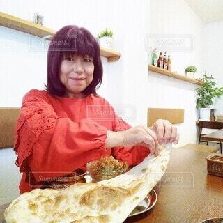 大好きなインドカレーに思わず笑顔になる60歳の女性の写真・画像素材[3869366]