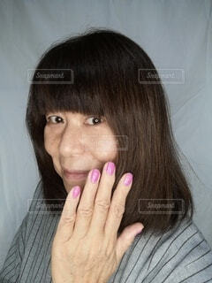 ネイルをした手と六十歳の女性の顔の写真・画像素材[3899276]