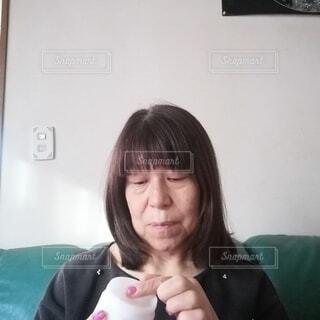 面倒くさそうに指にクリームをつける60歳の女性の写真・画像素材[3909188]