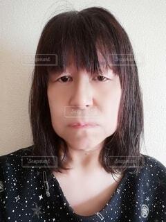口を尖らせて怒りをあらわにする60歳の女性の写真・画像素材[3941182]