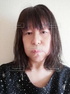 口を尖らせて不満げな表情をする60歳の女性の写真・画像素材[3941179]