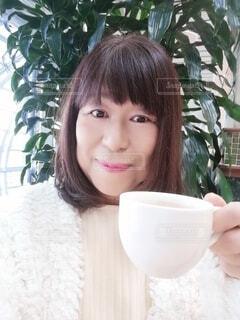 コーヒーカップを手にしてくつろぐ六十歳の女性の写真・画像素材[4000284]