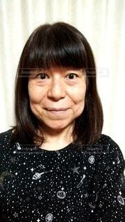 正面を向いて微笑む60歳の女性の写真・画像素材[4112401]