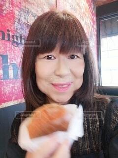 嬉しそうにハンバーガーを手に持つ60歳の女性の写真・画像素材[4320606]