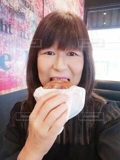 ハンバーガーを食べる60歳の女性の写真・画像素材[4320607]