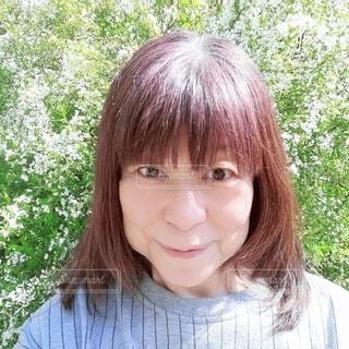 綺麗な花を見て微笑む六十歳の女性の写真・画像素材[4352239]