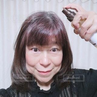 頭皮用のスプレーをする60歳の女性の写真・画像素材[4371859]