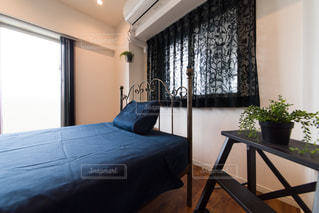 ガラスブロック張りの明るい寝室。ベッドルーム。アンティークのアイアンベッド。観葉植物。脚立。青いドア。扉。無垢のフローリング。の写真・画像素材[2688401]