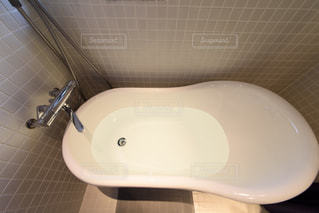 白いモザイクタイル張りの浴室。猫脚のバスタブ。窓のあるバスルーム。浴室。観葉植物。の写真・画像素材[2688526]