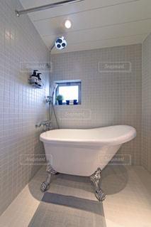 白いモザイクタイル張りの浴室。猫脚のバスタブ。窓のあるバスルーム。浴室。観葉植物。の写真・画像素材[2688527]