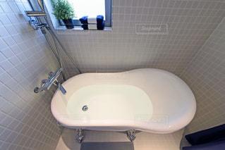 白いモザイクタイル張りの浴室。猫脚のバスタブ。窓のあるバスルーム。浴室。観葉植物。タオル。の写真・画像素材[2688530]