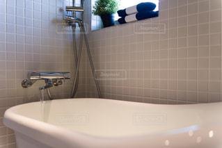 白いモザイクタイル張りの浴室。猫脚のバスタブ。窓のあるバスルーム。浴室。観葉植物。タオル。の写真・画像素材[2688535]