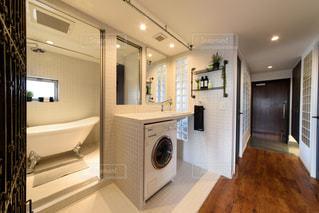 白いモザイクタイル張りの浴室。ビルトインの洗濯機。洗面所。大きな鏡。猫脚のバスタブ。窓のあるバスルーム。浴室。観葉植物。タオル。の写真・画像素材[2688578]