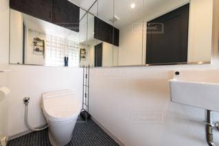 ガラスブロック張りのトイレ。手洗い付きの広いレストルーム。タンクレストイレ。大きな鏡張りの写真・画像素材[2688680]