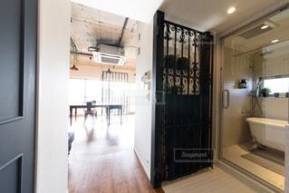 バロックモチーフのアイアンパーテーション。白いタイル張りの洗面所。ビルトイン洗濯機。ガラス張りの浴室。の写真・画像素材[2688712]