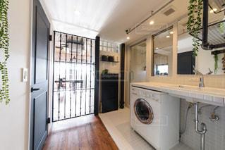 バロックモチーフのアイアンパーテーション。白いタイル張りの洗面所。ビルトイン洗濯機。ガラス張りの浴室。白い壁。青いドア。の写真・画像素材[2688714]