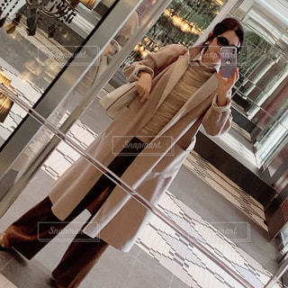 鏡の隣に立っている人の写真・画像素材[2705692]