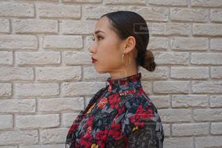レンガ壁の前に立っている女性の写真・画像素材[757496]