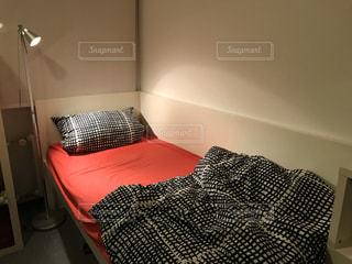 赤い毛布付きのベッドの写真・画像素材[3279904]