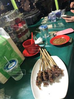 食べ物の皿を持ってテーブルに座っている人の写真・画像素材[2704428]