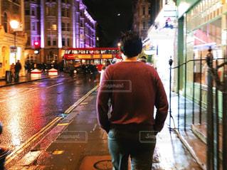 夜の濡れた街の通りにいる男の写真・画像素材[2963716]