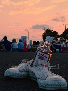 花火大会の待ち時間。お酒を飲みながら夕日を眺める。の写真・画像素材[2974810]