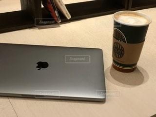 テーブルの上に座っているラップトップ コンピューターノートパソコンとコーヒーの写真・画像素材[1549936]