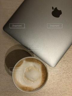 テーブルの上のコーヒー カップとノートパソコンの写真・画像素材[1549938]