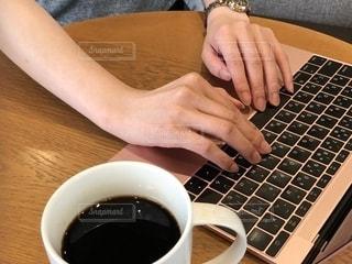 一杯のコーヒーとテーブルの上に座っているラップトップ コンピューターを操作する女性の手の写真・画像素材[1549986]