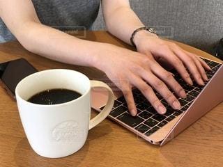 コーヒー カップの上に座っているラップトップ コンピューターを使用している女性の手の写真・画像素材[1549989]