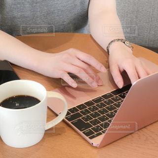 ノート パソコンと一杯のコーヒー テーブルに座っている女性の手の写真・画像素材[1549990]