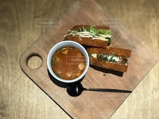 木製テーブルの上に食品のスープボウルとサンドイッチの写真・画像素材[1550057]