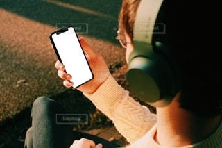 動画や音楽を聴きながらスマートフォンを見る男性の写真・画像素材[2737105]