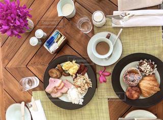 木製のテーブルの上に座っている食べ物の束の写真・画像素材[2736707]