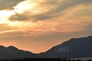 山を背景にした水域の夕日の写真・画像素材[2736930]