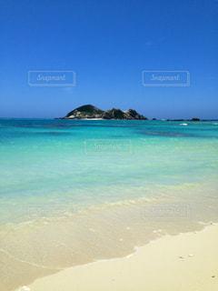 海の隣のビーチの上に座っている青いフリスビーの写真・画像素材[2833387]