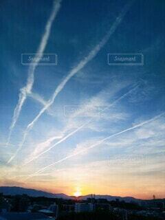 夕日と飛行機雲の写真・画像素材[4363931]