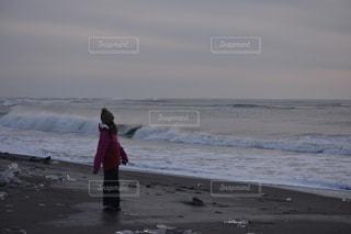 冬の浜辺にたたずむ少女の写真・画像素材[2777043]