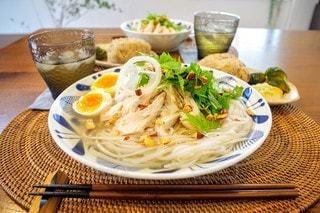 食べ物の皿をテーブルの上に置くの写真・画像素材[3555407]
