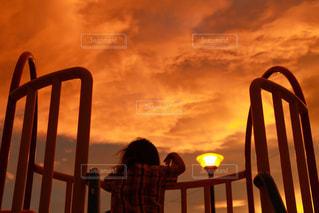 フェンスの前の椅子に座っている人の写真・画像素材[2426201]