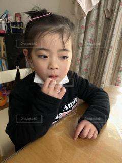 テーブルの上に座っている小さな子供の写真・画像素材[2794096]